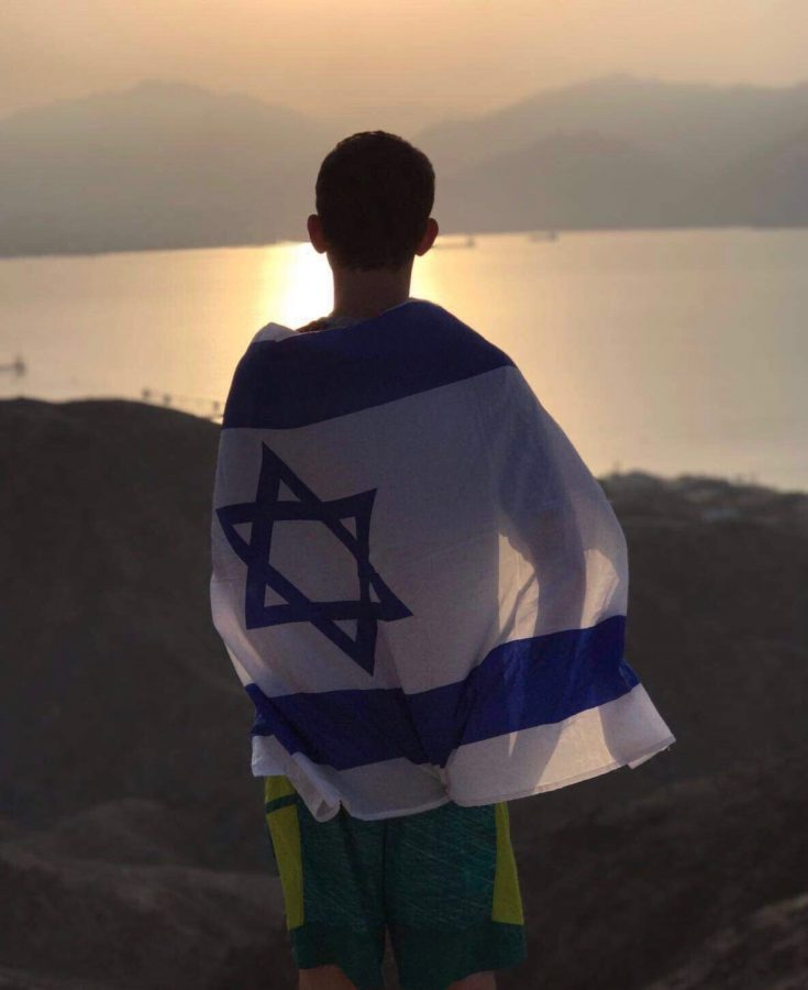 Jonah+Gershman+%28%E2%80%9819%29+overlooks+the+Red+Sea+in+Eilat%2C+Israel.+The+Israeli+flag+wrapped+around+his+back+showcases+his+patriotism+to+the+country+where+will+enlist+into+the+Israeli+Defense+Forces+later+this+year.